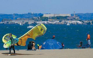 Κολυμβητής με kiteboard περπατάει στην παραλία μπροστά από τη νήσο Αλκατράζ, στο Σαν Φρανσίσκο.