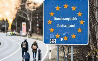 Δύο ταξιδιώτες περνούν πεζή τα σύνορα ανάμεσα στην Αυστρία και στη Γερμανία, στον μεθοριακό σταθμό του Σάρνιτς, λίγο μετά την επιβολή των περιοριστικών μέτρων, στα μέσα Μαρτίου.