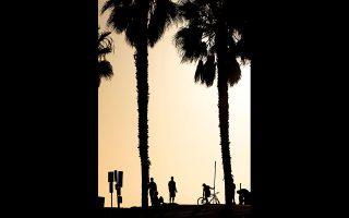 Κάτοικοι του Σαν Ντιέγκο τηρούν τις αποστάσεις καθώς ο ήλιος δύει στην παραλία της πόλης.