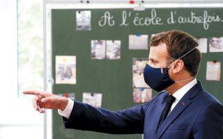 Φορώντας προστατευτική μάσκα, από την οποία δεν λείπουν τα χρώματα της γαλλικής σημαίας, ο Εμανουέλ Μακρόν απευθύνεται σε μαθητές δημοτικού σχολείου στο Πουασί.