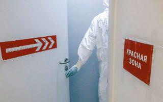 Yγειονομικός υπάλληλος ανοίγει μια πόρτα σε κλινική της Μόσχας, ειδικευμένη στη θεραπεία ασθενών με COVID-19.