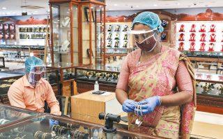 Πωλήτρια με μάσκα και ασπίδα προστασίας προσώπου σε κοσμηματοπωλείο της Κολκάτα, στην Ινδία (φωτ. από REUTERS).
