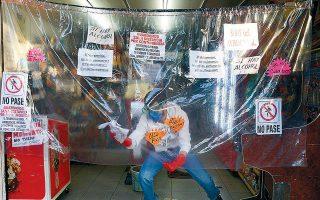Ανδρας καθαρίζει ένα πλαστικό κάλυμμα στο μαγαζί του στην Πόλη του Μεξικού.