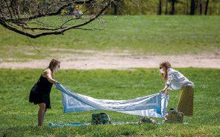 Nεοϋορκέζες, φορώντας μάσκα, απλώνουν τις κουβέρτες τους στο πάρκο Πρόσπεκτ του Μπρούκλιν.