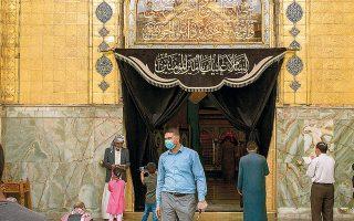 Φύλακας ασφαλείας με μάσκα στέκεται στην είσοδο του ναού του ιμάμη Αλι στη Νατζάφ, την ιερή πόλη των σιιτών, στο Ιράκ.