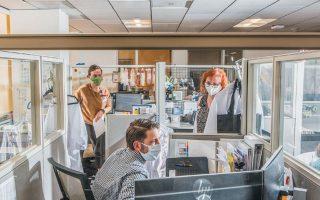 Εργαζόμενοι στο γραφείο πρόληψης μολύνσεων στο Πανεπιστήμιο της Καλιφόρνιας δουλεύουν μέσα σε προστατευτικά κουβούκλια.