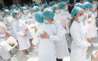 Κινέζες νοσηλεύτριες αγκαλιάζονται στη διάρκεια τελετής για την Παγκόσμια Ημέρα Νοσηλευτικού Προσωπικού στην πολύπαθη Γουχάν.