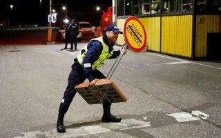 Eσθονός αστυνομικός απομακρύνει το προειδοποιητικό σήμα, καθώς ανοίγουν εκ νέου τα σύνορα μεταξύ των χωρών της Βαλτικής.