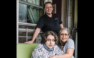 Ο 14χρονος Τζακ Μακμόρο και οι γονείς του στο μπαλκόνι του σπιτιού τους στο Κουίνς μετά το εξιτήριο από το νοσοκομείο.
