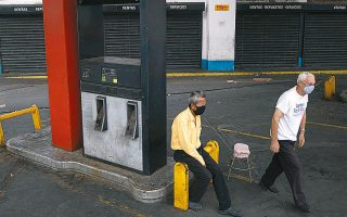 Δύο άνδρες έξω από κλειστό πρατήριο καυσίμων στο Καράκας.