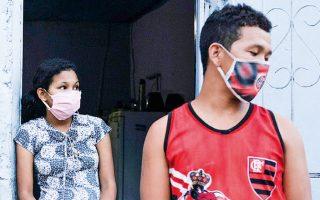 Συγγενείς ανθρώπου με Αλτσχάιμερ που πέθανε με πυρετό και δυσκολία στην αναπνοή στο Μανάους της Βραζιλίας φορούν μάσκες, έξω από το σπίτι του (φωτ. από A.P.).