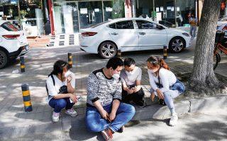 Κινέζοι σε προάστιο του Πεκίνου με μάσκες εν μέσω της πανδημίας.