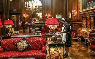 Καθαρίστρια που φοράει προστατευτική μάσκα ξεσκονίζει στο λόμπι του παραδοσιακού ξενοδοχείου Sacher στη Βιέννη.