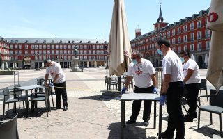 Workers use measuring tape to check social distancing as they set up a terrace which will be allowed to open from May 25, amid the coronavirus disease (COVID-19) outbreak, at Plaza Mayor Square in Madrid, Spain, May 24, 2020. REUTERS/Sergio Perez
