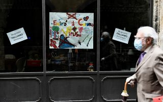 FILE PHOTO: A man wearing a face mask walks next to a shop, as the spread of the coronavirus disease (COVID-19) continues in Bergamo, Italy May 13, 2020. The signs reads