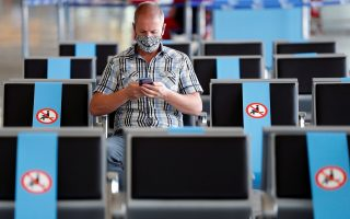 A man wearing a protective face mask sits at Fiumicino Airport, where new security measures have been implemented ahead of a further loosening of movement restrictions on June 3, when Italy is due to reopen its borders to travellers from Europe to unwind its rigid lockdown due to the coronavirus disease (COVID-19), in Rome, Italy, May 28, 2020. REUTERS/Guglielmo Mangiapane