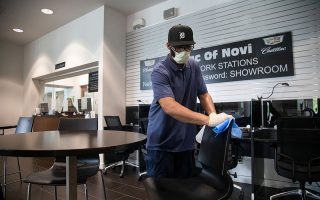 An employee wearing a protective mask wipes down chairs and tables inside the auto showroom at the Cadillac of Novi dealership amid an outbreak of the coronavirus disease (COVID-19) in Novi, Michigan, U.S., May 27, 2020. REUTERS/Emily Elconin