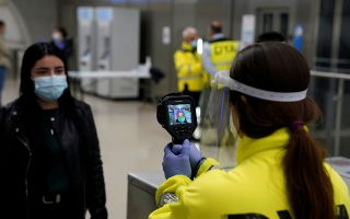 A member of the voluntary ambulance service organisation DYA (Detente y Ayuda) uses a thermal imaging camera to take the temperature of a train passenger, as half of Spain enters 'Phase 1' with the easing of one of Europe's strictest coronavirus disease (COVID-19) lockdowns, in Bilbao, Spain, May 11, 2020. REUTERS/Vincent West