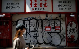 FILE PHOTO: A woman wearing a protective face mask, following an outbreak of the coronavirus disease (COVID-19), walks in front of a temporary closed ramen noodle restaurant after the government announced the state of emergency for the capital following the disease outbreak in Tokyo, Japan April 8, 2020.  REUTERS/Issei Kato/File Photo