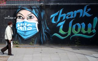 A person wearing a protective face mask walks past streetart 'NHS Dedication Mural' by The Artful Dodger (A.Dee) in Elephant & Castle, following the outbreak of the coronavirus disease (COVID-19), London, Britain, May 5, 2020. REUTERS/Hannah McKay