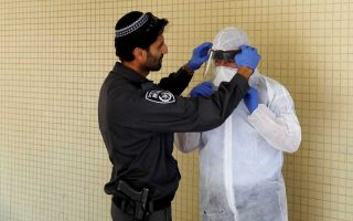 An Israeli police officer helps a Health Ministry inspector put on protective gear before they go up to the apartment of a person in self quarantine as a precaution against coronavirus spread in Hadera, Israel March 16, 2020 REUTERS/Ronen Zvulun - RC23LF9W400M