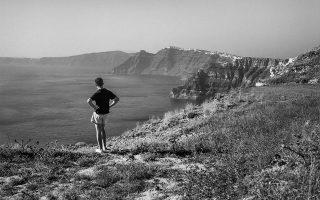 Ο νεαρός άνδρας που κοιτάζει προς την Καλντέρα είναι ο φίλος του Ρόμπερτ και του Τσαρλς Μακέιμπ, Πέτρος Νομικός. Χάρις στον Σαντορινιό αυτόν, τα δύο αδέλφια ήρθαν στην Ελλάδα και επισκέφτηκαν το νησί. ROBERT A. McCABE