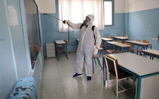 A municipal worker wearing personal protective equipment (PPE) disinfects a school, on the first day of the easing of a nationwide lockdown against the spread of the coronavirus disease (COVID-19), in Athens, Greece, May 4, 2020. REUTERS/Goran Tomasevic