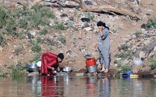 Aιγύπτιες πλένουν πιάτα και άλλα χρηστικά αντικείμενα στον Νείλο.
