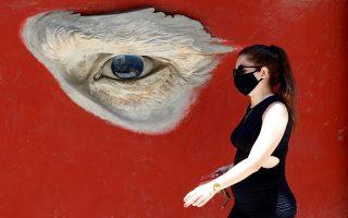 Κοιτώντας. Με την μάσκα της η νεαρή Κουβανή περνά από τοιχογραφία στην Αβάνα που θυμίζει πολύ την αυτοπροσωπογραφία του Βίνστεντ βαν Γκόγκ σε κατακόκκινο φόντο.  EPA/Ernesto Mastrascusa