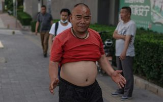 Το μπικίνι του Πεκίνου. Ετσι αποκαλείται η συνήθεια (γιατί μόδα δεν το λες) των ανδρών στην πρωτεύουσα της Κίνας. Δηλαδή τις ημέρες που κάνει ζέστη να μαζεύουν την μπλούζα τους ψηλά, ακριβώς κάτω από το στήθος – δεν μπορείς να κυκλοφορείς και γυμνός στην πόλη- και να αφήνουν την στρογγυλή ή όχι κοιλίτσα τους να δροσίζεται.  EPA/WU HONG