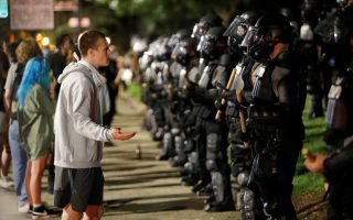 A protester pleads with riot police during nationwide unrest following the death in Minneapolis police custody of George Floyd, in Raleigh, North Carolina, U.S. May 31, 2020. Picture taken May 31, 2020. REUTERS/Jonathan Drake