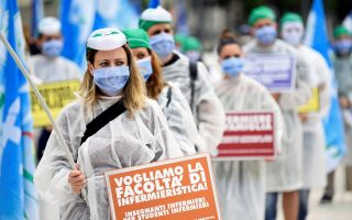 Medical workers in an area of Milan hard-hit by the coronavirus disease (COVID-19) outbreak, wearing protective suits and masks, hold placards as they attend a demonstration to demand more financial help from the government and to honour the victims of the virus, in Milan, Italy, June 10, 2020. REUTERS/Flavio Lo Scalzo