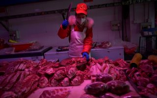 FILE PHOTO: An employee chops pork meat at the Xinfadi wholesale market, as the country is hit by an outbreak of the novel coronavirus disease (COVID-19), in Beijing, China February 19, 2020. REUTERS/Tingshu Wang/File Photo