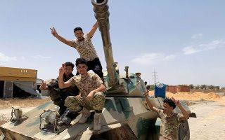 Ανδρες των δυνάμεων που υποστηρίζουν την κυβέρνηση της Τρίπολης πανηγυρίζουν πρόσφατες στρατιωτικές επιτυχίες τους έξω από τη λιβυκή πρωτεύουσα (φωτ. REUTERS).