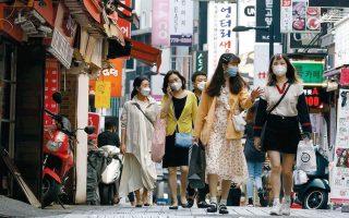 Στη Σεούλ, την πρωτεύουσα της Νότιας Κορέας, χώρας που τα έχει πάει καλά στην αντιμετώπιση της COVID-19, οι πολίτες οφείλουν να έχουν μαζί τους μία απλή χειρουργική μάσκα και μία πιο ανθεκτική, τύπου Ν95, την οποία πρέπει να φορούν σε περιστάσεις συνωστισμού.  (Φωτ. REUTERS / KIM HONG-JI)