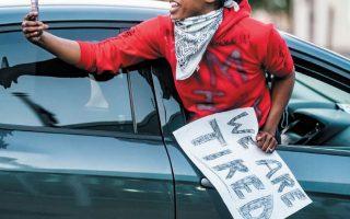 Επάνω, διαδηλωτής καταγράφει με το κινητό του πορεία στη Μινεάπολη για τη δολοφονία του Τζορτζ Φλόιντ. Κάτω, Αφροαμερικανός στο Λούισβιλ διαμαρτύρεται για την αστυνομική βία με το σύνθημα «Κουραστήκαμε πια».