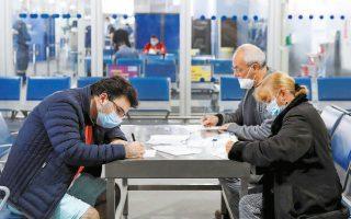 Επιβάτες στο αεροδρόμιο «Ελ. Βενιζέλος» συμπληρώνουν τα απαραίτητα έγγραφα μετά την άφιξή τους στην Ελλάδα.