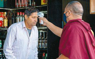 Εξόριστος βουδιστής μοναχός στην Ινδία χρησιμοποιεί ψηφιακό θερμόμετρο για να διαπιστώσει εάν ο άνθρωπος απέναντί του έχει πυρετό (φωτ. A.P.).
