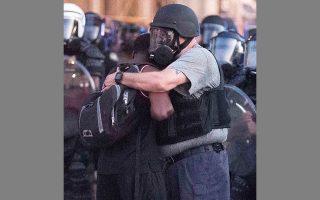 Αστυνομικός αγκαλιάζει διαδηλώτρια που βοήθησε να διαλυθεί πλήθος στην Ατλάντα.