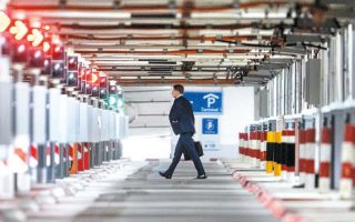 Eνας άνδρας βαδίζει μόνος μέσα σε έρημο πάρκινγκ του αεροδρομίου της Φρανκφούρτης, στη Γερμανία.