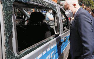 Ο Γερμανός υπουργός Εσωτερικών Χορστ Ζεεχόφερ επιθεωρεί τις καταστροφές σε αυτοκίνητο της αστυνομίας στη Στουτγάρδη.