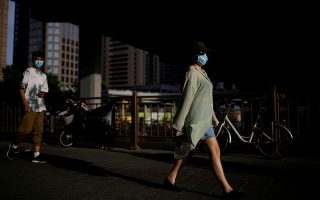 FILE PHOTO: FILE PHOTO: People wearing face masks following the coronavirus disease (COVID-19) outbreak walk under an overpass in Beijing, China June 4, 2020. REUTERS/Carlos Garcia Rawlins/File Photo/File Photo