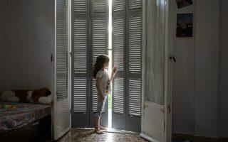 Μία από τις κόρες της οικογένειας κοιτάζει έξω από τα μισόκλειστα παντζούρια. (Φωτοφραφία: ENRI CANAJ)
