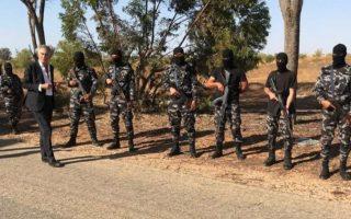 Ο Μπερνάρ-Ανρί Λεβί πλαισιωμένος από ένοπλους άνδρες με αυτόματα όπλα AK-47 και καλυμμένα πρόσωπα.