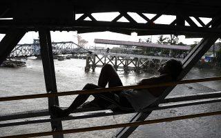 Μια ανάπαυλα. Πάνω στις σκαλωσιές κοντά στον ποταμό Yangon στην Μιανμάρ βρήκε καταφύγιο ο άνδρας της φωτογραφίας. Μια αφορμή για περισυλλογή μέχρι να σταματήσει η βροχή. EPA/LYNN BO BO