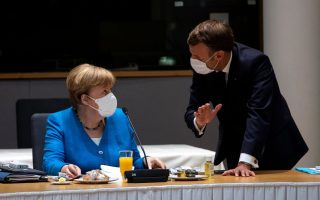 German Chancellor Angela Merkel speaks with France's President Emmanuel Macron during a meeting on the sidelines of the first face-to-face EU summit since the coronavirus disease (COVID-19) outbreak, in Brussels, Belgium July 18, 2020. Francisco Seco/Pool via REUTERS