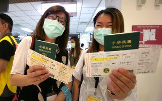 Ταϊβανέζες δείχνουν τα διαβατήρια και τις κάρτες επιβίβασής τους στην εικονική πτήση που κέρδισαν, έπειτα από κλήρωση, στο αεροδρόμιο της Σονγκσάν. © AP Photo/Chiang Ying-ying