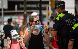 Aστυνομικός στη Βαρκελώνη κάνει παρατήρηση σε μια μαμά που κυκλοφορεί με το παιδί της και τους ζητάει να φορέσουν μάσκα, καθώς το μέτρο είναι πλέον υποχρεωτικό στην Καταλωνία. Στο μεταξύ, η Σερβία ανακοίνωσε χθες την απαγόρευση συναθροίσεων άνω των δέκα ατόμων και τον περιορισμό λειτουργίας εσωτερικών χώρων εστιατορίων και καφέ μέχρι τις 9 το βράδυ. (Φωτ. A.P. PHOTO / EMILIO MORENATTI)