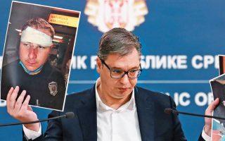 O Σέρβος πρόεδρος Αλεξάνταρ Βούτσιτς δείχνει φωτογραφίες τραυματιών αστυνομικών καθώς εξηγεί, σε διάγγελμά του, πώς εκτυλίχθηκαν τα επεισόδια στο Βελιγράδι μετά την ανακοίνωση επαναφοράς του lockdown. Απέδωσε τη βία σε ακροδεξιά στοιχεία και ξένες δυνάμεις και δεσμεύθηκε ότι θα πατάξει κάθε προσπάθεια κατάλυσης της έννομης τάξης. Μετά τις αντιδράσεις, πάντως, ο Βούτσιτς υπαναχώρησε και προανήγγειλε την επιβολή μερικών περιοριστικών μέτρων που ανακοινώνονται σήμερα. (Φωτ. REUTERS / MARKO DJURICA)