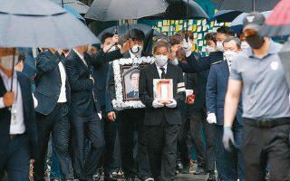 Ανδρας, κρατώντας το πορτρέτο του Παρκ, ηγείται της πομπής από το δημαρχείο της Σεούλ προς το νεκροταφείο, για την κηδεία του. (φωτ. A.P.)